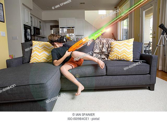 Young boy on sofa, wearing virtual reality headset, firing laser guns, digital composite