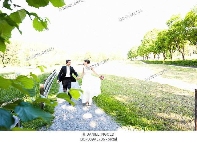 Bride and bridegroom running along park path