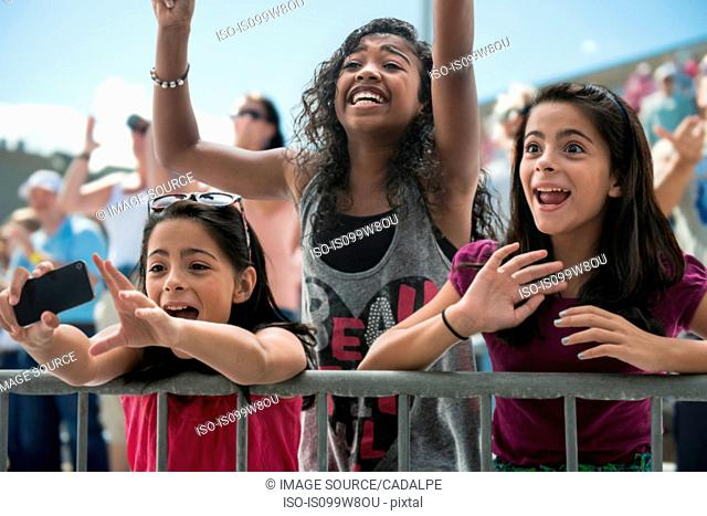 Three excited girls at a pop concert