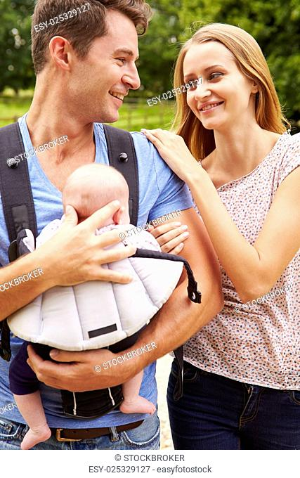 Parents With Baby In Carrier On Walk In Countryside