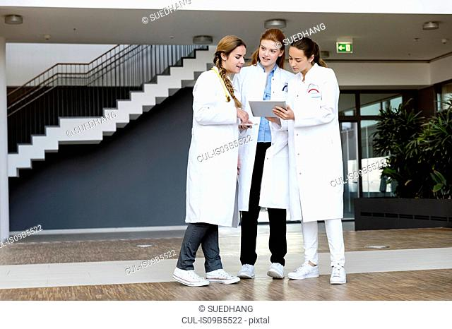 Three doctors looking at digital tablet