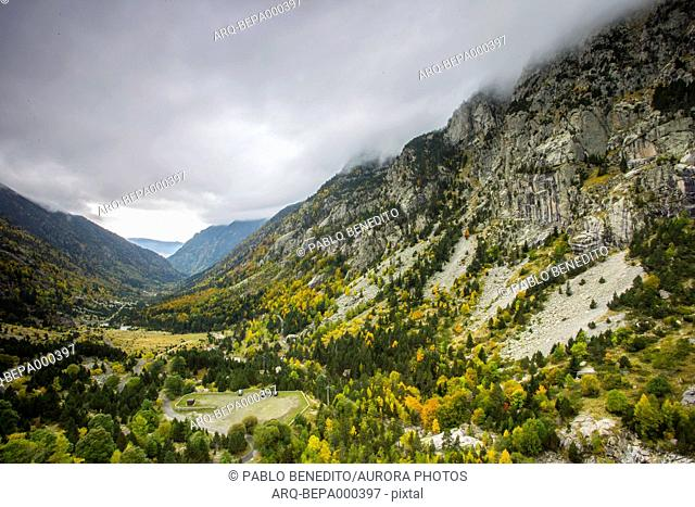 Clouds over trees in valley of Aiguestortes i Estany de Sant Maurici National Park during autumn, Cavallers, Lleida, Spain