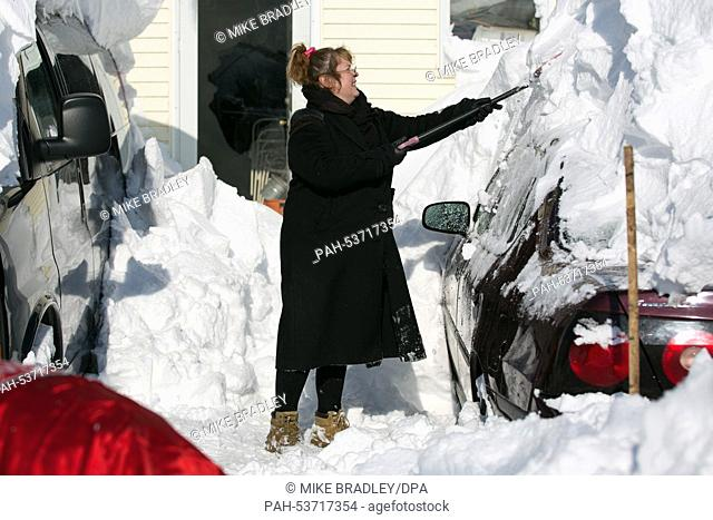 Christyann Mutka shovels snow off of her car in Alden, New York, USA on Wednesday, November 19, 2014. Up to six feet of snow fell on the region Tuesday