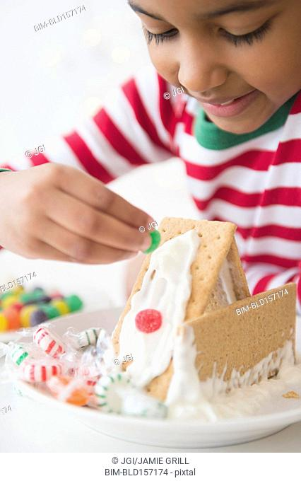 Mixed race girl decorating gingerbread house