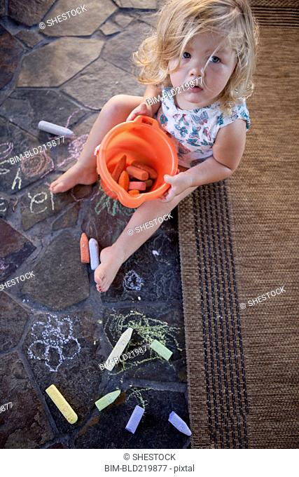 High angle view of girl drawing with chalk on tile