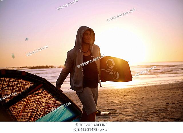 Man in hoody carrying kiteboard equipment on sunset beach