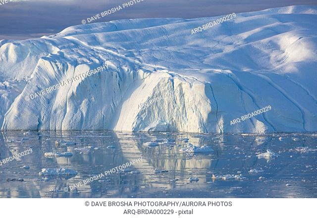 A huge iceberg (some of the icebergs can be the size of city blocks) sits in the Ilulissat Icefjord in Greenland after it has broken off from the Greenland...