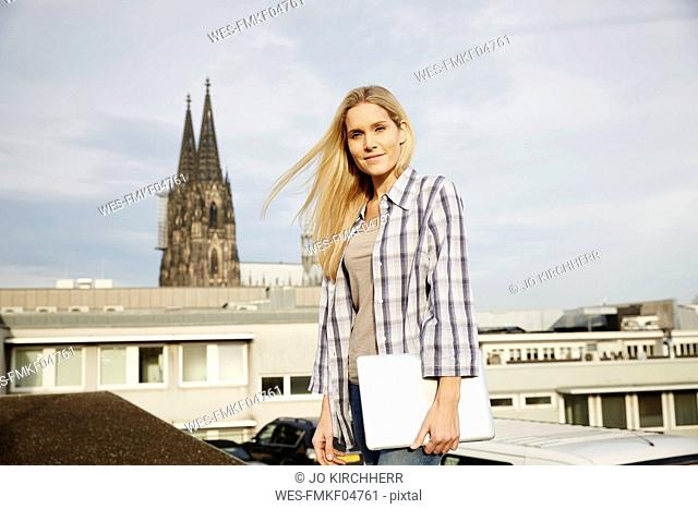 Germany, Cologne, portrait of smiling blond woman with laptop