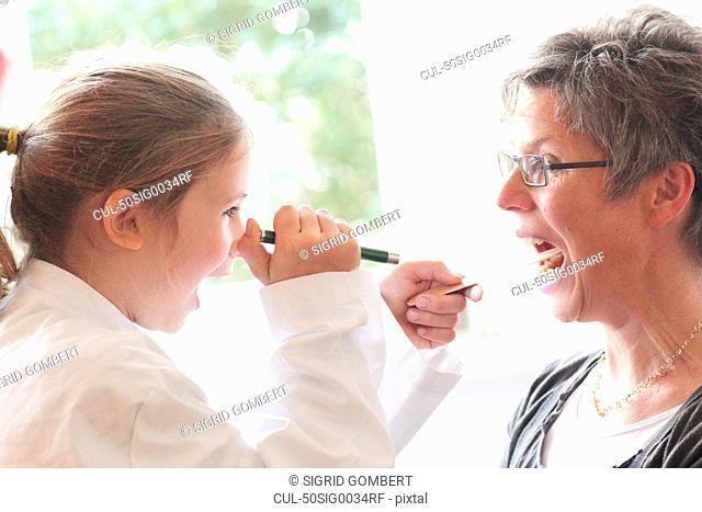 Girl playing doctor with grandmother
