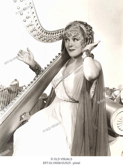 Woman in ancient Greek costume playing harp
