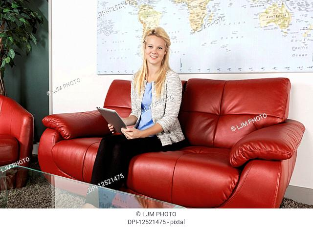 A beautiful young millennial business woman with long blond hair using her tablet in the lobby of a workplace while waiting for a job interview and posing for...