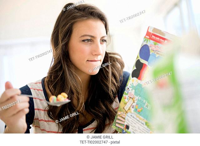 Woman eating cereal reading info on box
