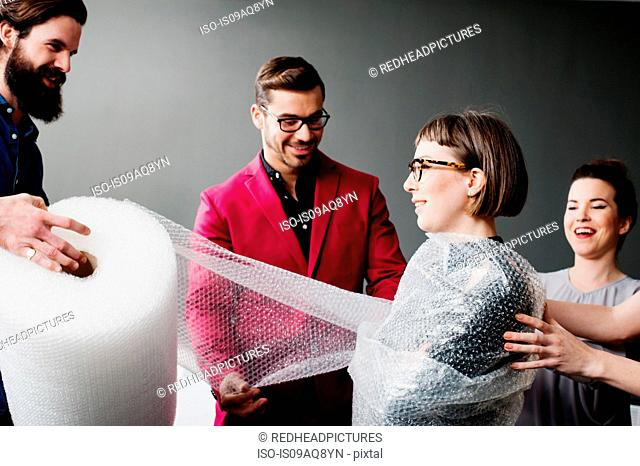 Young man wrapping woman in bubblewrap