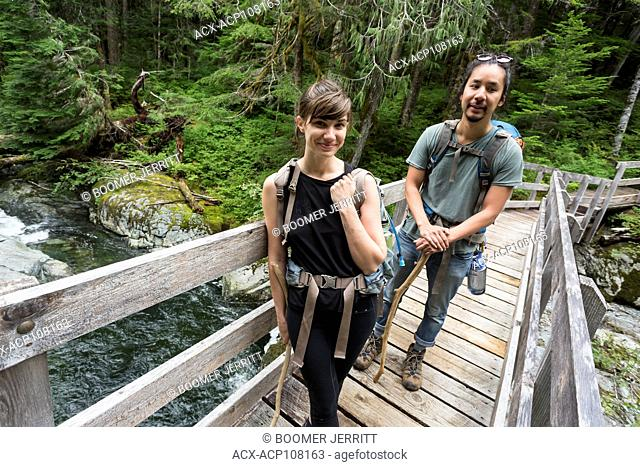 A young couple hiking out from Bedwell Lake crosses a footbridge near the end of the trail, Strathcona Park, Central Vancouver Island, British Columbia, Canada