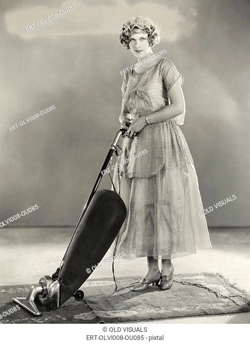 Woman vacuuming rug (OLVI008-OU085-F)