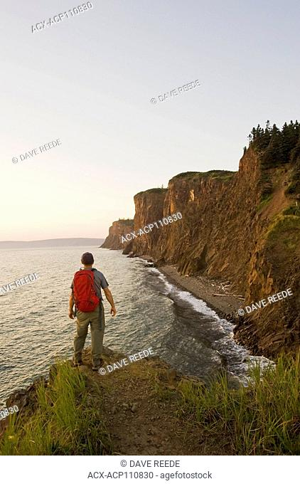 a hiker looks out over Cape d'Or, Bay of Fundy, Nova Scotia, Canada