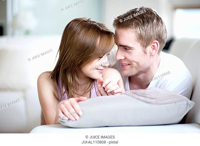 Young couple lying together on sofa, smiling