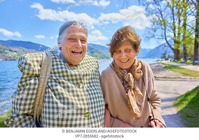 Happy two senior woman laughing heartily together