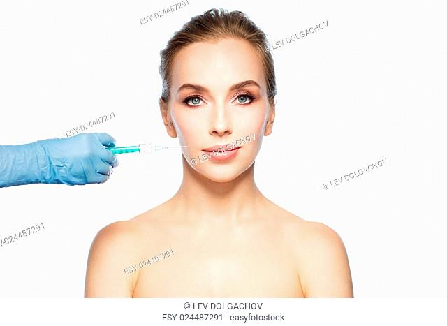 people, cosmetology, plastic surgery and beauty concept - beautiful young woman face and beautician hand in glove with syringe making injection over white...