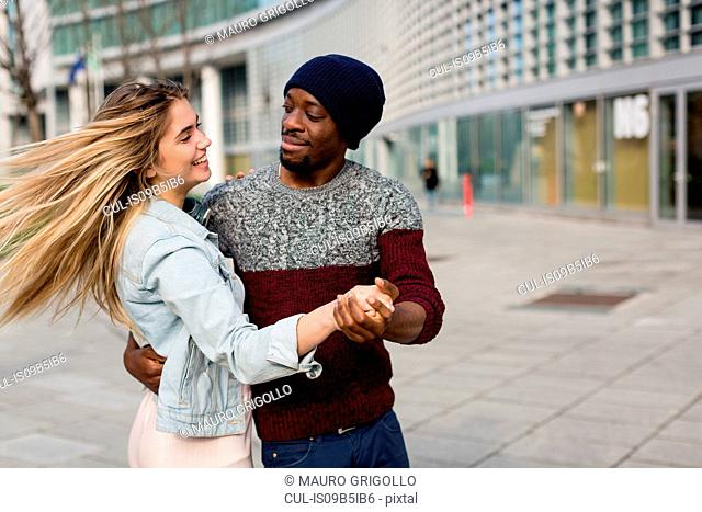 Young man and woman, outdoors, dancing, smiling