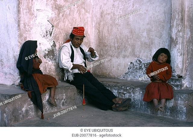 Taquile man spinning wool with his two children sitting either side of him