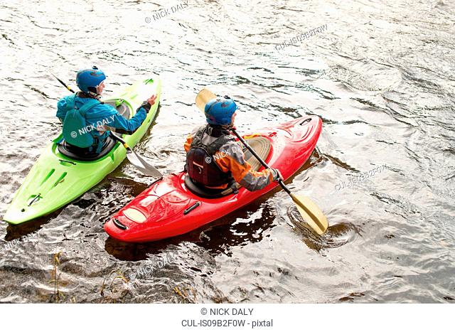 Male and female kayakers paddling on River Dee