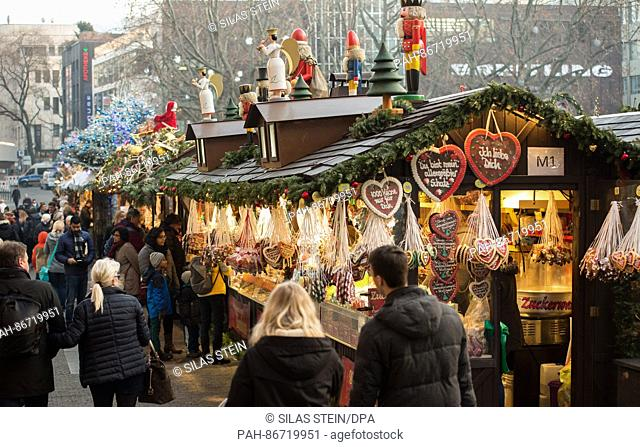 Vistors to the Christmas market walk past the stands in Stuttgart, Germany, 21 December 2016. The Christmas market will remain open until 23 December 2016