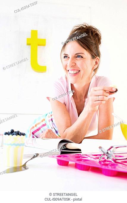 Mature woman resting on elbow holding baked product looking away smiling