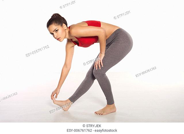 Woman athlete limbering up doing stretching exercises to warm her muscles before doing a workout