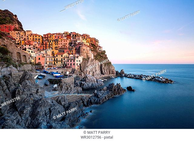 Beautiful sunset light shines on the colourful town of Manarola during a long exposure, Manarola, Cinque Terre, UNESCO World Heritage Site, Liguria, Italy