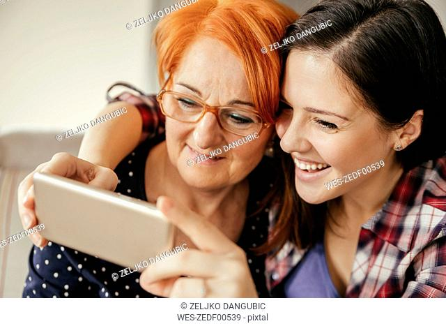 Happy adult daughter with mother taking a selfie