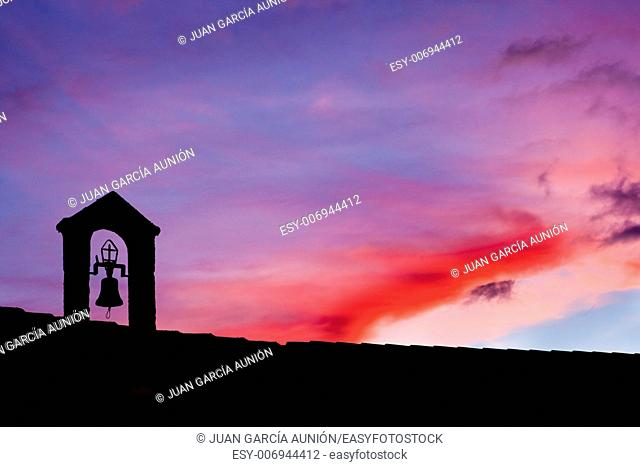 silhouette of Old belfry lighted with the last ray of light at sunset , Montanchez, Spain