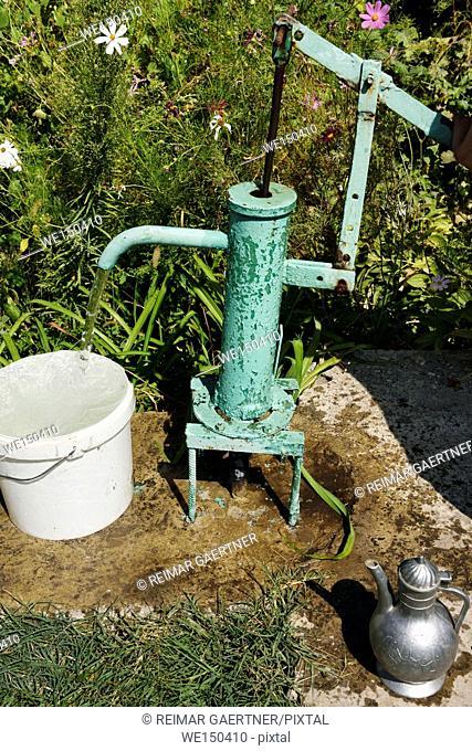 Hand pump with flowing water beside a garden in Shymkent South Kazakhstan Region