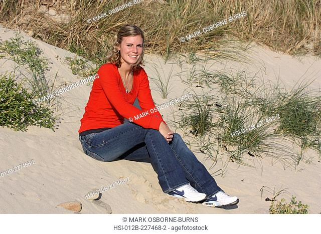 Young blonde woman outdoors. Sitting on sand dune at the beach