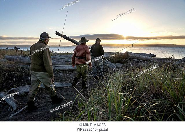 Two fly fisherman and a guide walk to a salt water beach at sunrise to fish for searun coastal cutthroat trout and salmon on a beach on the west coast of the...