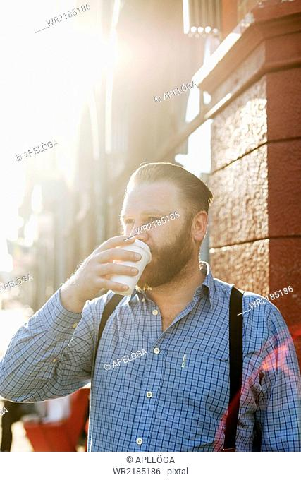 Businessman looking away while drinking coffee from disposable cup outdoors