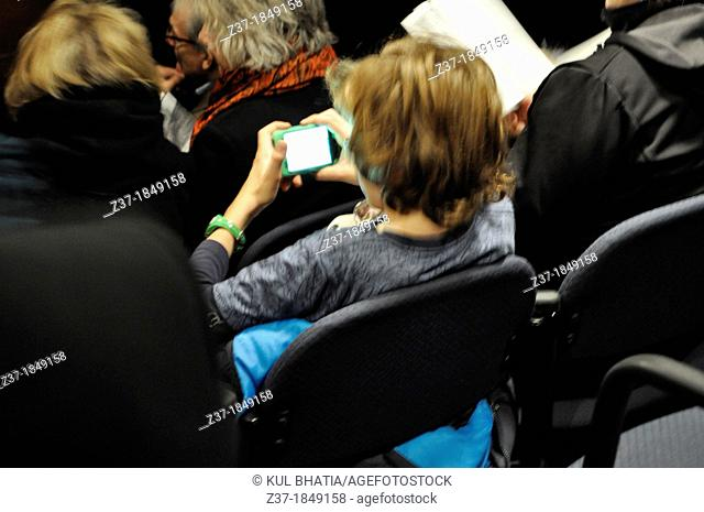 A young boy plays games on his smart phone before show time, Ontario, Canada