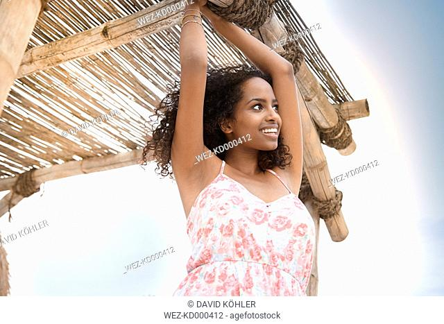 Happy young woman at thatched hut