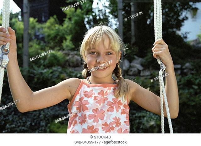 Blonde Girl sitting on Swing - Garden - Summer