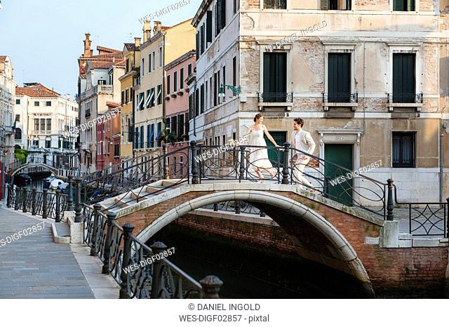 Italy, Venice, bridal couple running on little bridge
