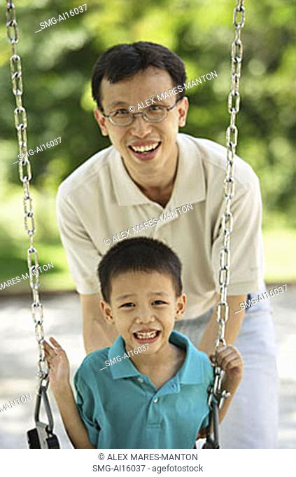 Boy on swing, father behind him, both smiling at camera
