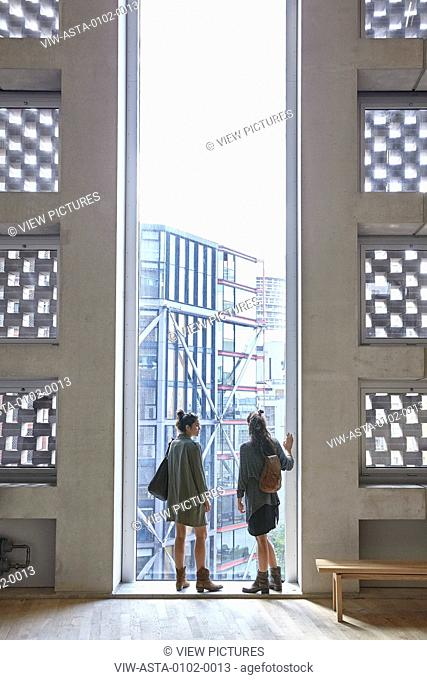 Two women look out over the city from a tall narrow window. SWITCH HOUSE AT TATE MODERN, London, United Kingdom. Architect: HERZOG & DE MEURON, 2016