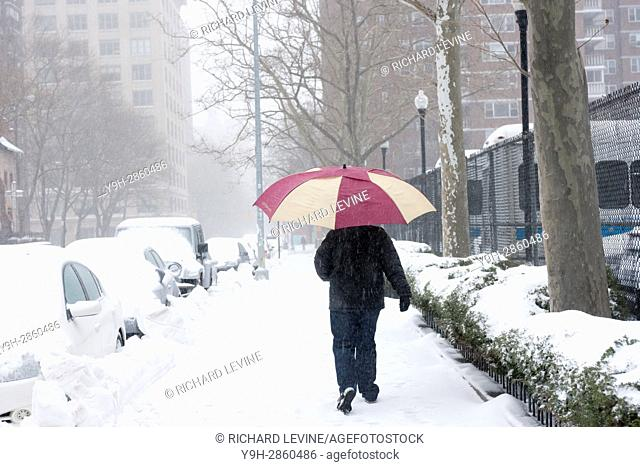 Pedestrians trudge through the snow in the Chelsea neighborhood of New York. Originally predicted as a blizzard with up to 20 inches of snow the storm has...