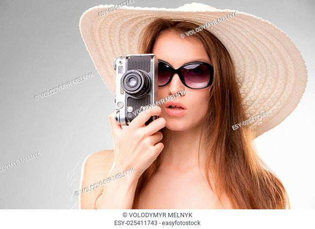 Girl in broad-brimmed hat and sunglasses with retro camera isolated on gray background