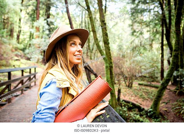 Young woman in trilby looking up from forest footbridge