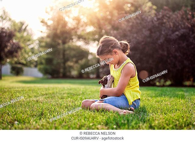 Girl sitting on grass holding Boston Terrier puppy