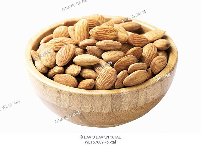 Close up of a wooden bowl of almonds isolated on a white background with a clipping path