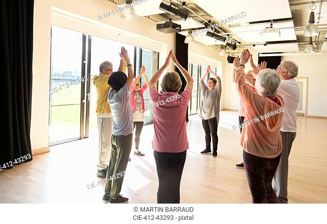 Active seniors exercising, stretching arms overhead in circle