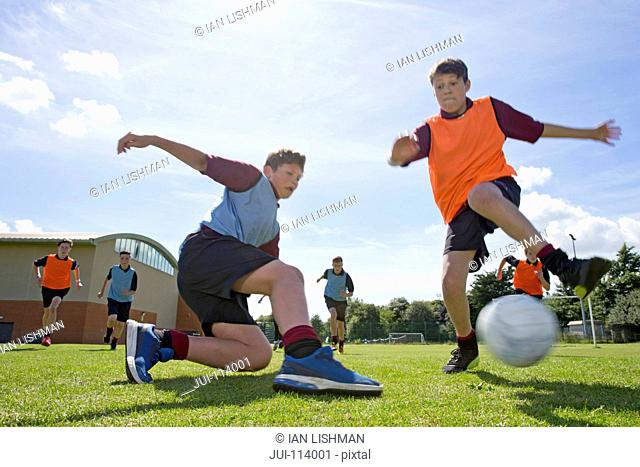 Middle schoolboys playing soccer on sunny field in physical education