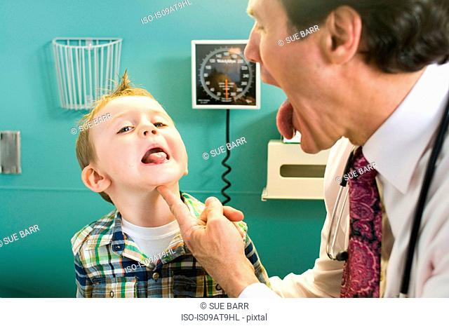 Male doctor looking at young boy's tongue